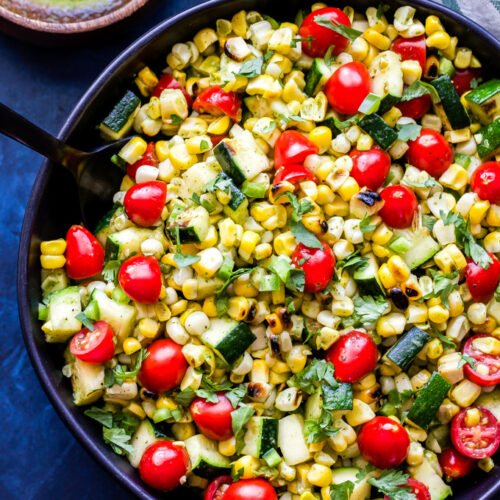 Grilled Zucchini Corn Tomato Salad in black bowl with black serving spoon
