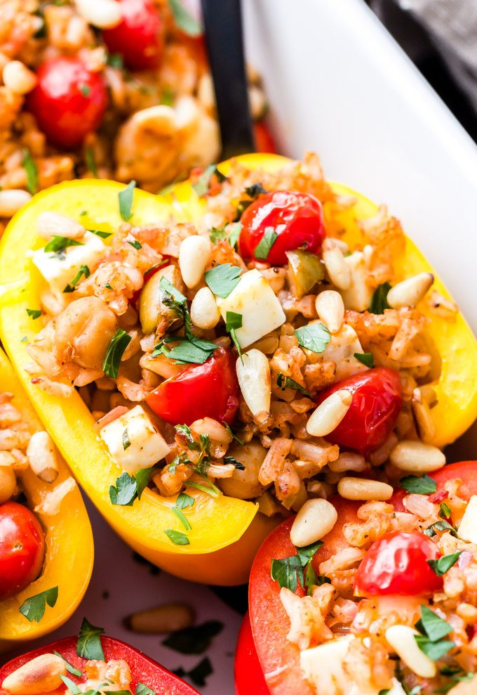 Mediterranean Stuffed yellow pepper in a white dish topped with tomatoes, feta and pine nuts.