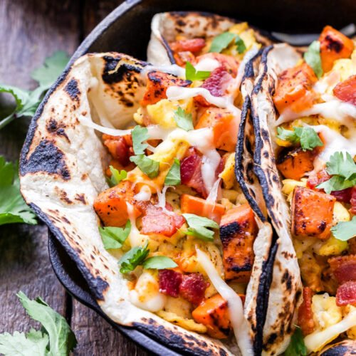 Sweet Potato, Bacon and Egg Breakfast Tacos topped with cheese in a cast iron skillet.