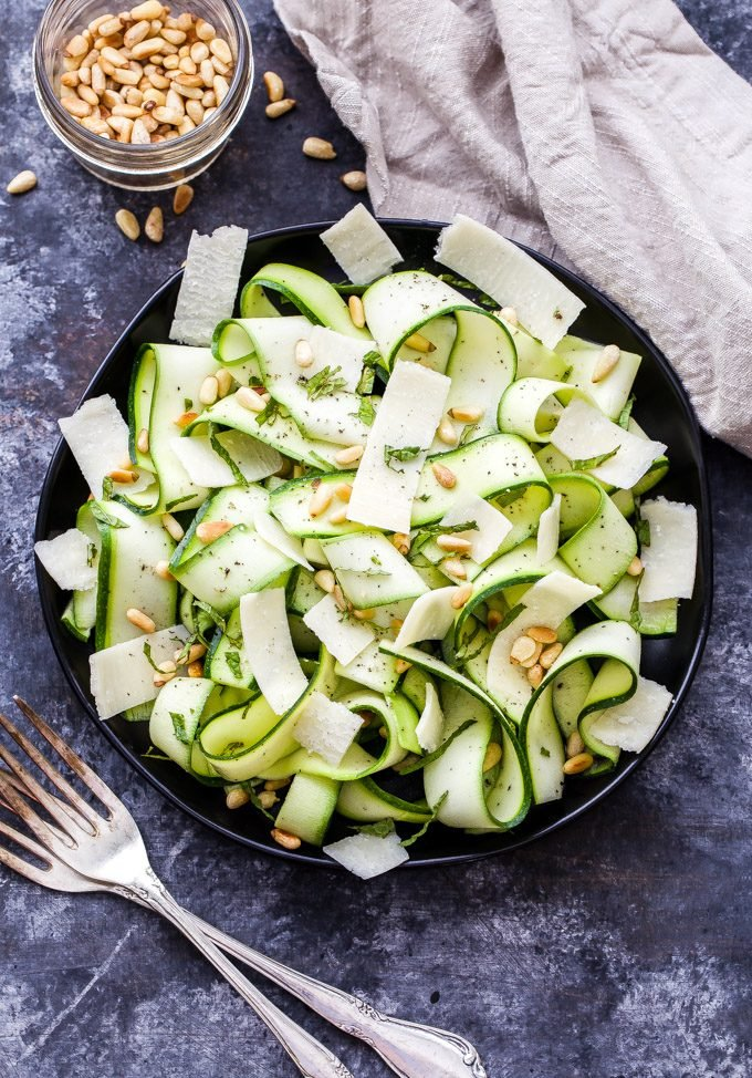 Zucchini Ribbon Salad with Lemon and Parmesan Cheese in black bowl with a small bowl of pine nuts on the side.