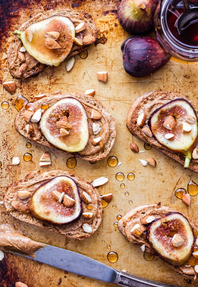 Fig and Almond Butter Toast will take your toast game to a whole new level! Whole grain bread topped with creamy almond butter, cinnamon, fresh figs, a drizzle of maple syrup and chopped almond for crunch. It's a game changing breakfast or snack! #figs #almondbutter #toast #breakfast #vegan