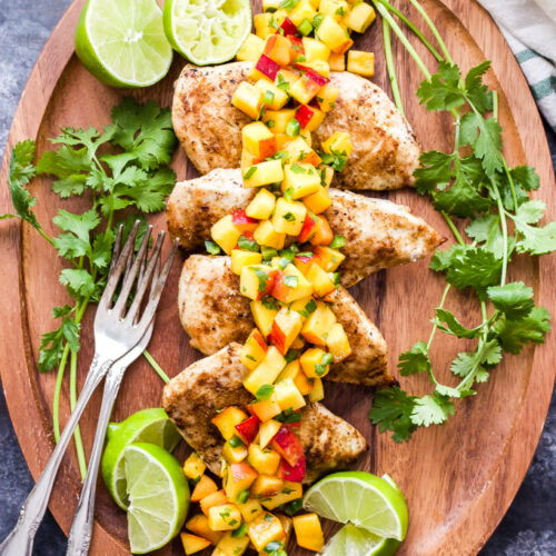 Grilled Cumin Chicken with Peach Salsa on wooden platter with limes and cilantro