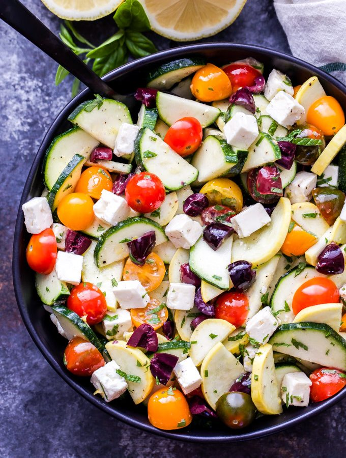 Mediterranean Zucchini, Tomato and Feta Salad is a fresh, light and easy to make summer salad. Tossed in a lemon herb vinaigrette, it's perfect for when your garden is overflowing with zucchini and tomatoes! #zucchini #tomatoes #salad #mediterraneanrecipe #glutenfree