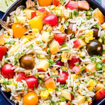 Summer Vegetable Orzo Salad overhead photo in black bowl with limes on the side