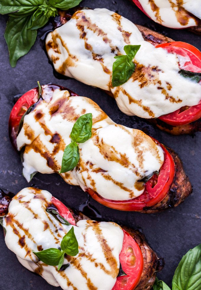 Caprese Balsamic Grilled Chicken is an easy and healthy dinner that's perfect for those sweet summer tomatoes! Balsamic marinated chicken breasts, thick slices of tomatoes, basil and fresh mozzarella. What's not to love?!  #chicken #caprese #capresechicken #grilledchicken #glutenfree