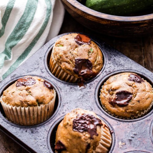 Chocolate Chunk Zucchini Muffins are the perfect way to use extra zucchini from your garden. Almond butter replaces the oil in these muffins and they're packed with shredded zucchini and dark chocolate chunks. A delicious way to start the morning!#muffins #zucchini #zucchinimuffins #chocolate #breakfast #almondbutter #brunch