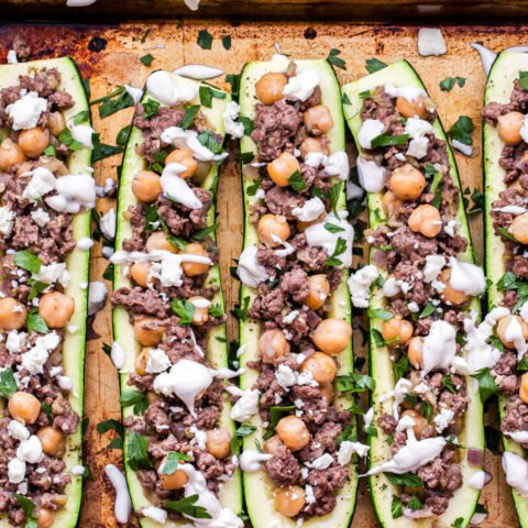 Lamb and Chickpea Stuffed Zucchini on a sheet pan drizzled with Tahini Yogurt Sauce.
