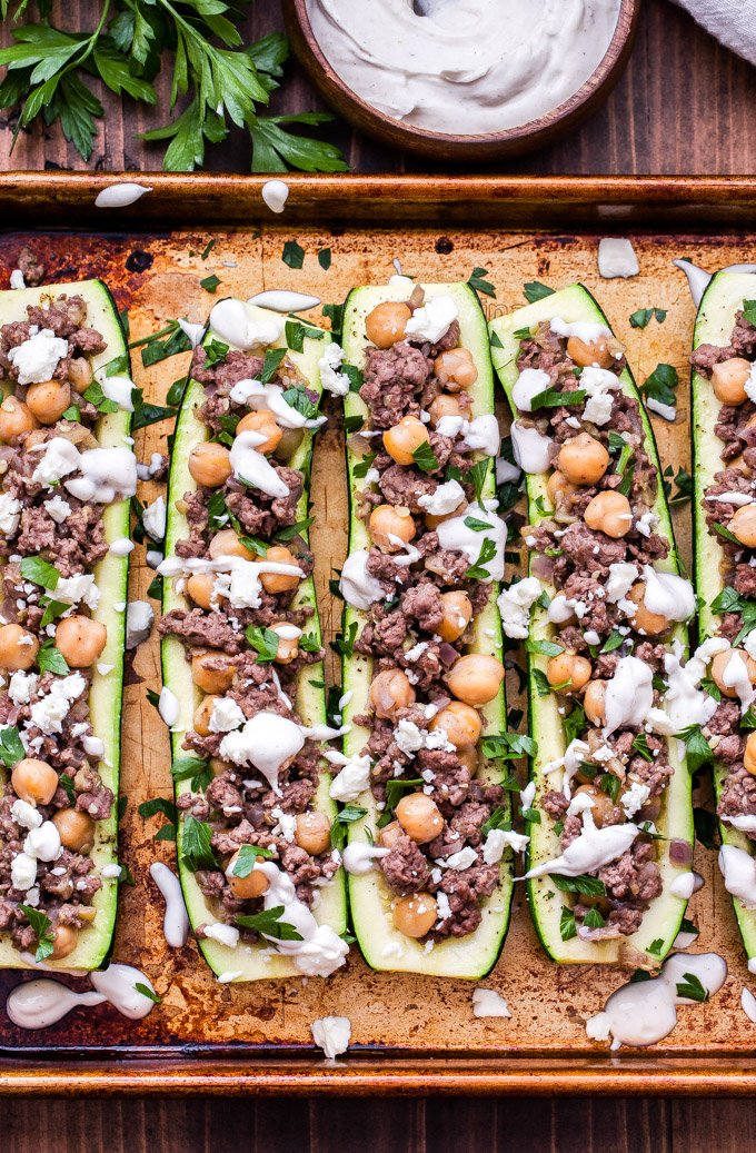 Lamb and Chickpea Stuffed Zucchini with Tahini Yogurt Sauce is a delicious and easy to make dinner that's perfect if you're new to cooking with or eating lamb. Warm, fragrant, spices such as cinnamon and allspice add wonderful flavor to this exotic, but comforting dish. #lamb #zucchini #mediterranean #healthydinner #lowcarb #chickpeas #tahini