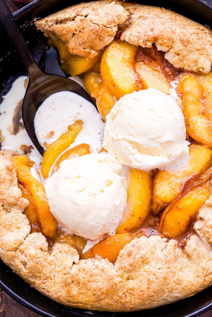 Skillet Peach Cobbler is the ultimate summer treat! A simple biscuit crust topped with fresh, sweet peaches and all baked in a cast iron skillet. Top with vanilla ice cream for the perfect bite! #peaches #peachcobbler #skillet #dessert