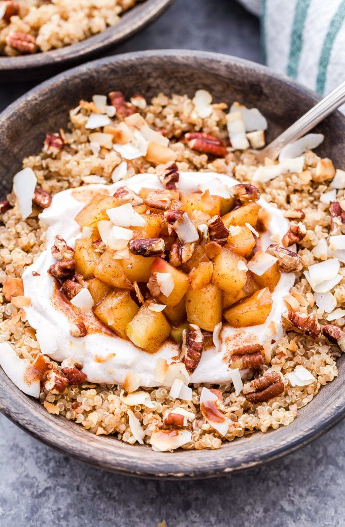 Quinoa topped with cinnamon apples and greek yogurt in a gray bowl.