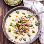 This Creamy Italian Cauliflower Soup is so thick and delicious that you'll forget you're eating soup. A low-carb alternative to potato soup, but just as satisfying thanks to the Italian sausage, pesto and Fontina cheese piled on top! #cauliflower #soup #cauliflowersoup #lowcarb #italian #glutenfree