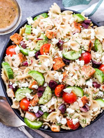 Greek Chicken Pasta Salad is a delicious and healthy main dish pasta salad that's great any time of year! Tossed in a red wine vinaigrette and loaded with cucumbers, tomatoes, kalamata olives and of course, plenty of feta cheese! #pasta #pastasalad #greekrecipe #chicken #feta #easyrecipe #healthydinner