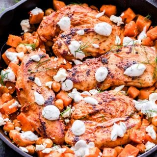 Harissa Chicken, Sweet Potato and Chickpea Skillet is a simple, satisfying and super flavorful dinner perfect for busy nights. Spicy from the harissa sauce, but balanced out by the sweet potatoes and cool, creamy, herb yogurt sauce. #harissa #chicken #sweetpotato #chickpeas #skilletrecipe #easydinner