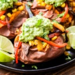 Veggie Fajita Stuffed Sweet Potatoes are great way to change up traditional fajitas. Baked sweet potatoes are topped with mushrooms, peppers and onions in a flavorful blend of Mexican spices. Top it with guacamole for a healthy and filling meatless dinner! #fajitas #sweetpotato #vegetables #vegan #glutenfree #healthydinner