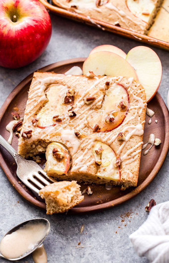 A square slice of the apple spice sheet pan pancakes on a wooden plate with a fork and apple slices