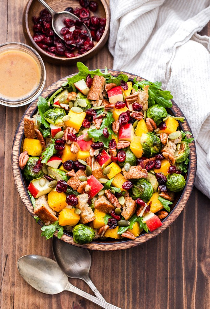 Fall Roasted Vegetable Panzanella Salad is made with butternut squash, brussels sprouts, apples, dried cranberries, pepitas and baby kale then tossed together in a cider vinaigrette. It's the perfect fall salad or colorful side dish for your Thanksgiving table! #panzanella #salad #brusselsprouts #butternutsquash #glutenfree #vegan #thanksgiving