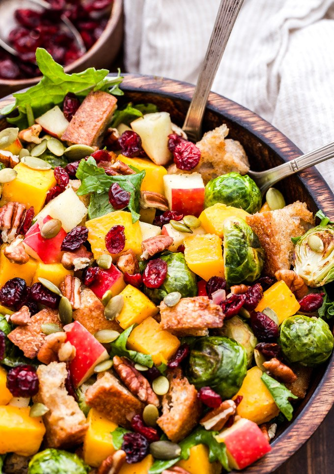 Fall Roasted Vegetable Panzanella Salad is made with butternut squash, brussels sprouts, apples, dried cranberries, pecan, pepitas and baby kale then tossed together in a cider vinaigrette. It's the perfect fall salad or colorful side dish for your Thanksgiving table! #panzanella #salad #brusselsprouts #butternutsquash #glutenfree #vegan #thanksgiving