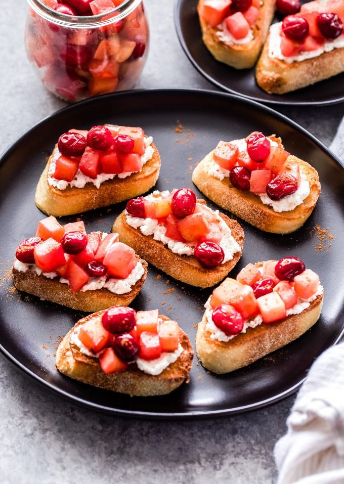 Six Goat Cheese Crostinis topped with Cranberry Apple Compote on a black serving plate with a jar of the compote behind them.