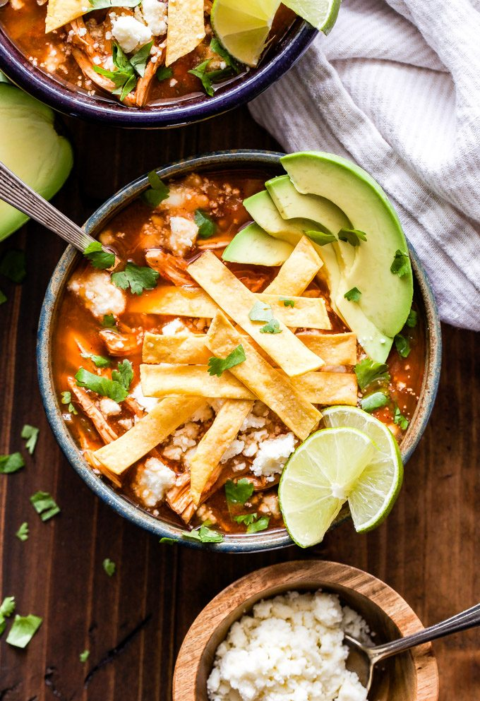 A bowl of chicken tortilla soup topped with tortilla strips, avocado slices, cilantro, limes and cheese.
