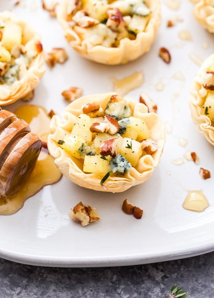 Apple, Blue Cheese, Pecan Bites in mini phyllo shells on white plate drizzled with honey.