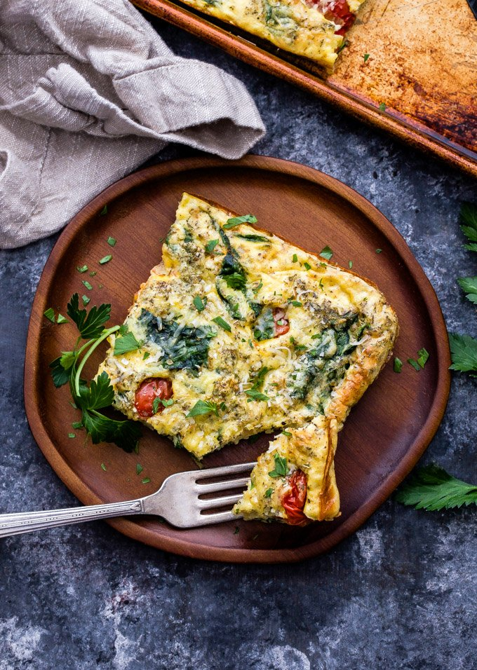 This Sheet Pan Spinach Tomato Ricotta Frittata is perfect for meal prep or feeding a group for breakfast. The savory Italian flavors are great for breakfast, lunch or dinner! #frittata #spinach #tomato #ricotta #vegetarian #breakfast #eggs #sheetpan #healthybreakfast