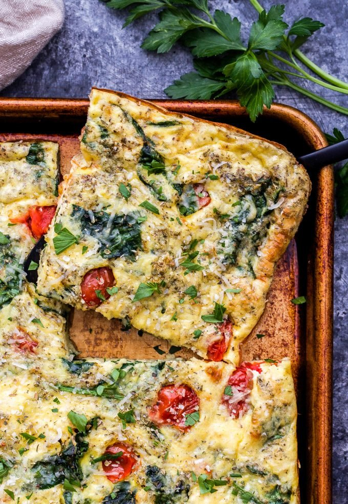 A square sliced of Sheet Pan Spinach Tomato Ricotta Frittata.
