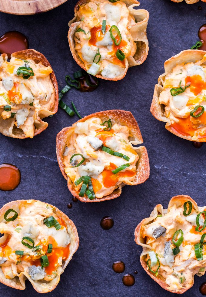 Baked Buffalo Chicken Wonton Cups are the perfect portable appetizer to serve for game day or your next party! You'll never suspect that the spicy, creamy, cheesy chicken filling was made with lighter ingredients! #buffalochicken #gameday #appetizer #superbowl #wontoncups #chicken