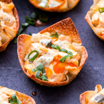 Five baked wonton cups filled with creamy buffalo chicken and topped with green onions, hot sauce and blue cheese crumbles.