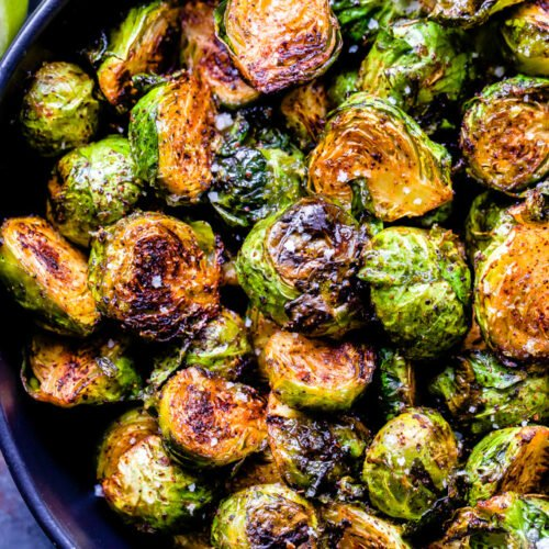 Closeup overhead photo of chili honey lime roasted brussels sprouts in a blue serving bowl.