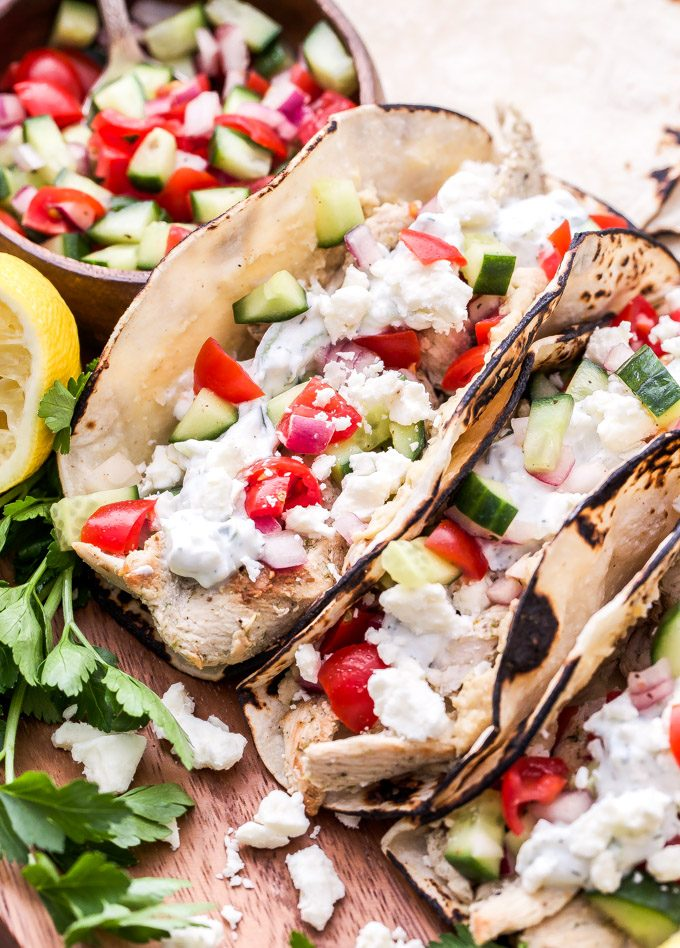 Two Greek chicken tacos on a wooden serving platter with tomato cucumber salad next to them in a small bowl.