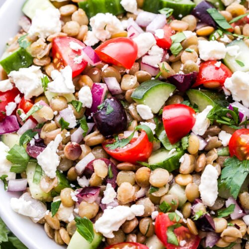 Mediterranean Lentil Salad in white bowl. Made with lentils, cucumbers, tomatoes, olives, feta and herbs.