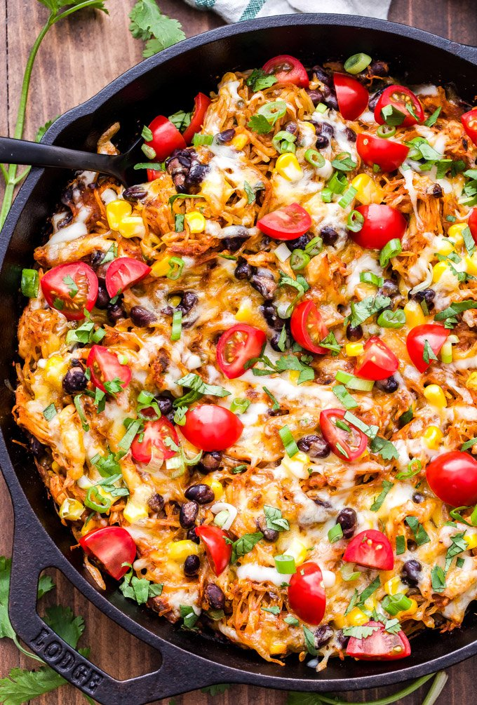 Southwest Spaghetti Squash Casserole is loaded with chicken, black beans, corn, enchilada sauce and topped with gooey melted cheese! A delicious and easy to make casserole that's gluten-free and a lower carb alternative to pasta or rice. #spaghettisquash #casserole #mexicanfood #chicken #glutenfree #lowcarb