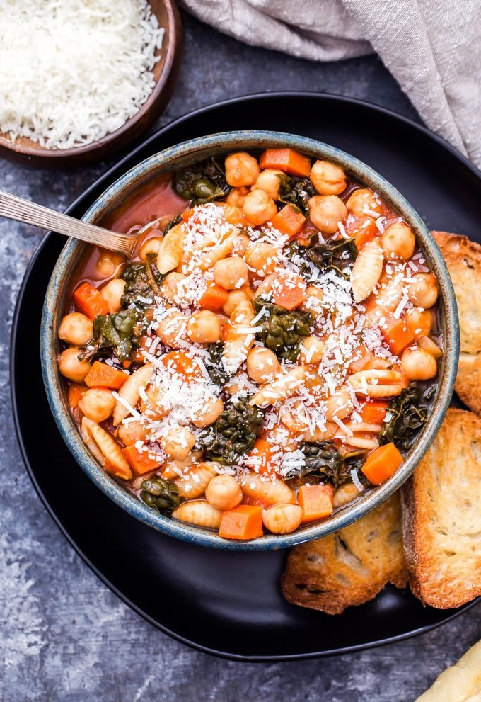 Chickpea pasta fagioli in a bowl with a spoon. The bowl is on a black plate with slices of baguette. A bowl of parmesan cheese is in the background.