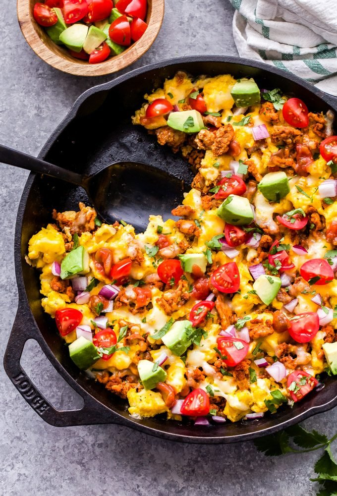 Overhead photo of cast iron skillet filled with ground turkey, scrambled eggs, tomatoes, avocado, cheese and Mexican spices. A serving has been scooped out and there is a black serving spoon in the skillet.