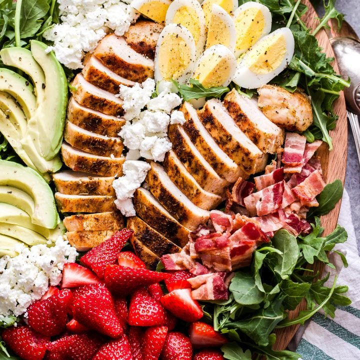 California Cobb Salad on platter with grilled chicken, strawberries, avocado slices, hard boiled eggs, bacon and goat cheese.