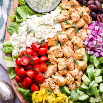 Chicken Souvlaki Salad on a platter with cucumbers, olives, red onion, feta, tomatoes, peppers and a bowl of dressing.