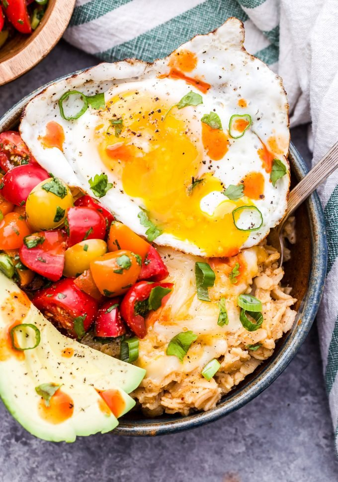 This Savory Southwest Oatmeal is a great way to change up your usual sweet oatmeal routine. Oatmeal seasoned with chili powder and cumin then topped off with avocado slices, cheese, tomatoes and an egg. Perfect for a hearty breakfast or even dinner! #oatmeal #savoryoatmeal #southwestrecipe #breakfast #glutenfree #egg #avocado