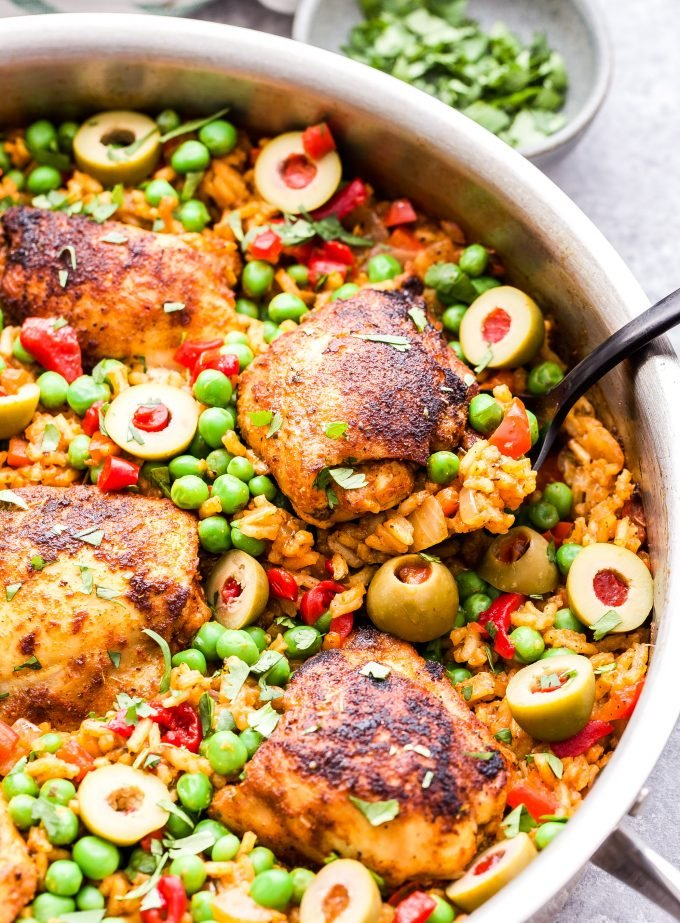 Arroz con Pollo with black spoon scooping chicken and rice