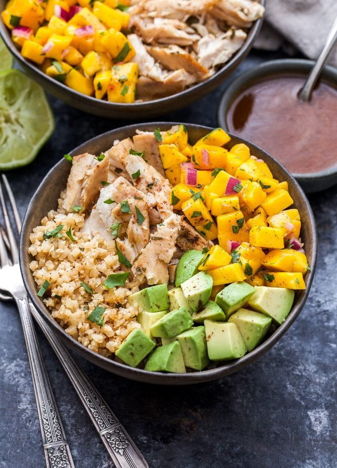 Cauliflower Rice Fish Taco Bowls topped with mango salsa and avocado