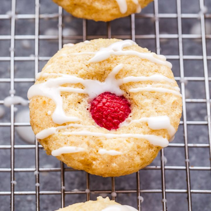 These mini Lemon Glazed Raspberry Muffins are perfect for spring brunch! Lemon flavored muffins topped with a fresh raspberry and drizzled with a sweet lemon glaze, you won't be able to eat just one! #muffins #raspberry #lemon #breakfast #brunch #minimuffin #Easter #MothersDay