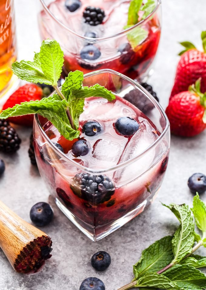 Mixed Berry Mint Julep in glass topped with berries and a fresh mint sprig
