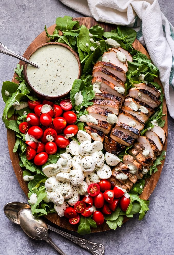 Caprese Grilled Chicken Salad on wood platter with dressing in a bowl