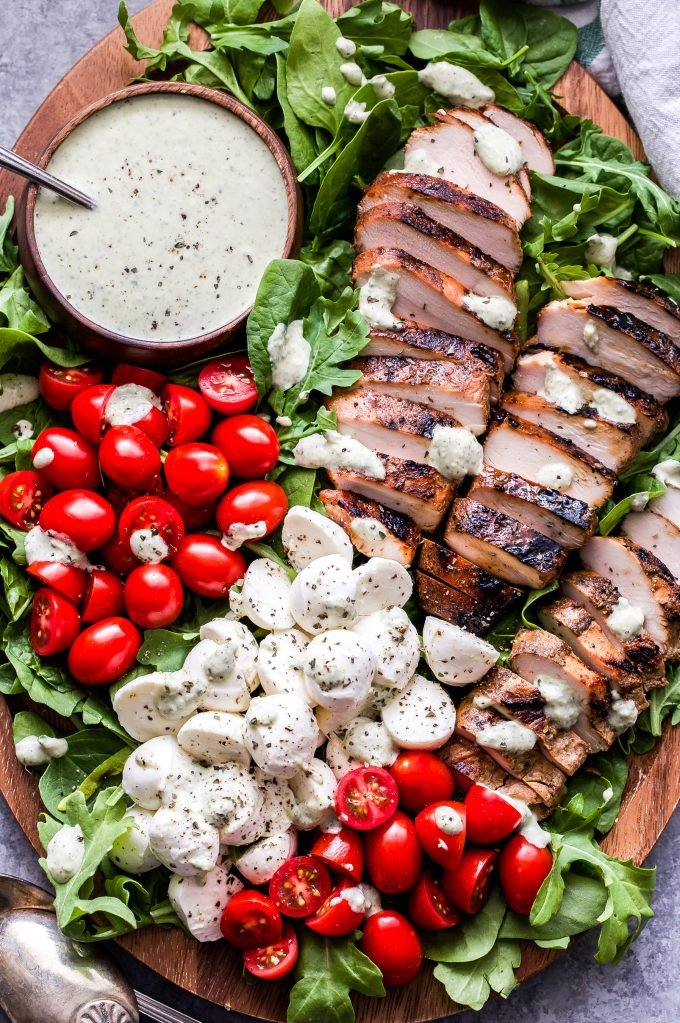 Caprese Grilled Chicken Salad on wood platter