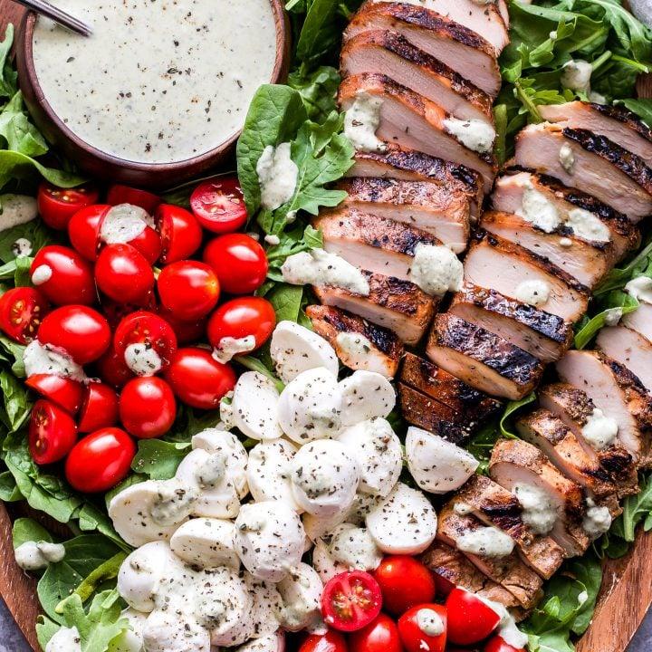 Caprese Grilled Chicken Salad on wood platter