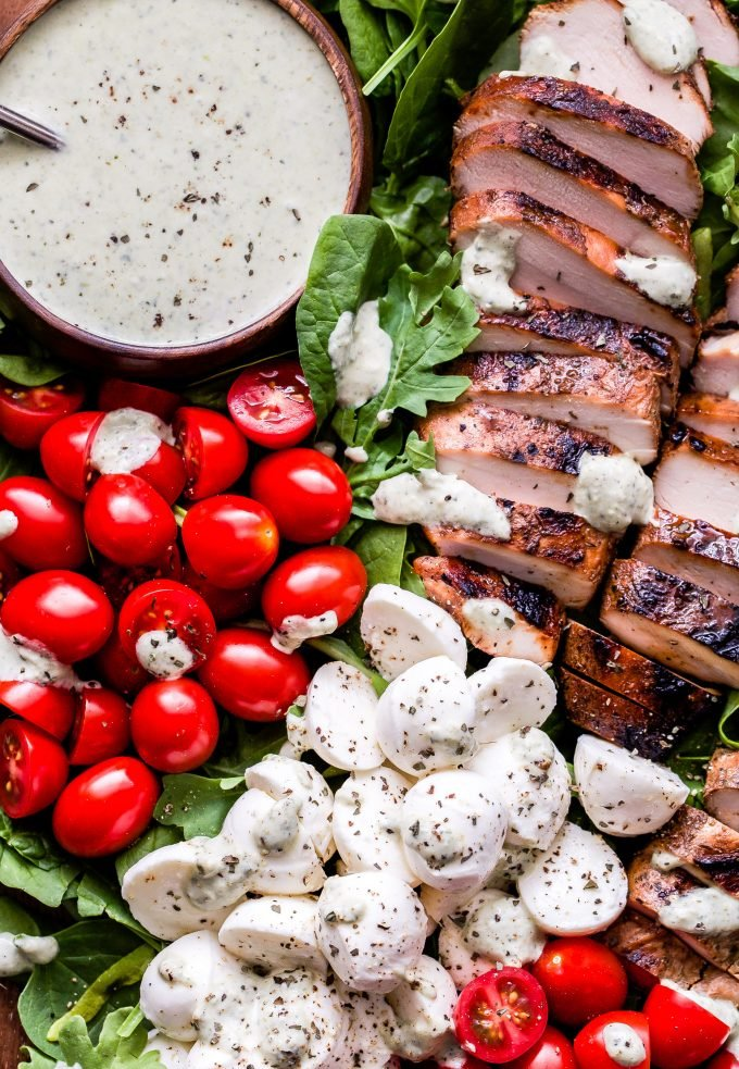 Caprese Grilled Chicken Salad with pesto dressing in a bowl