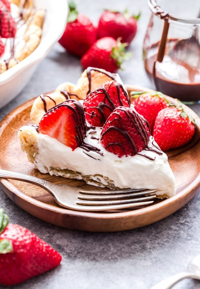 Chocolate Drizzled Strawberries and Almond Cream Pie sliced on wooden plate