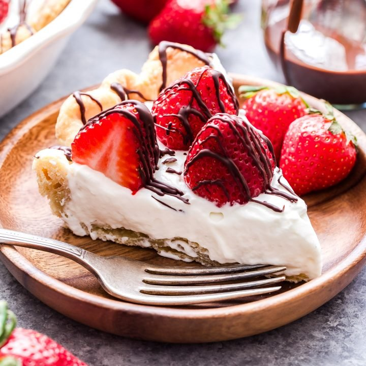 Chocolate Drizzle Strawberries and Almond Cream Pie sliced on wooden plate