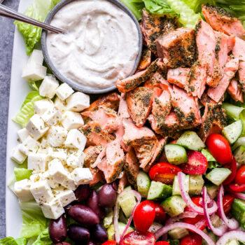 Greek Salmon Salad with Tahini Yogurt Dressing on white platter