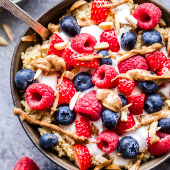 Berry Quinoa Breakfast Bowls topped with berries, Greek yogurt and almond butter