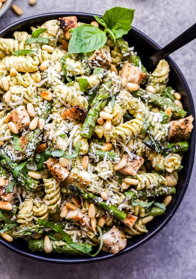 Grilled Chicken and Asparagus Pesto Pasta in black serving bowl with black serving spoon.